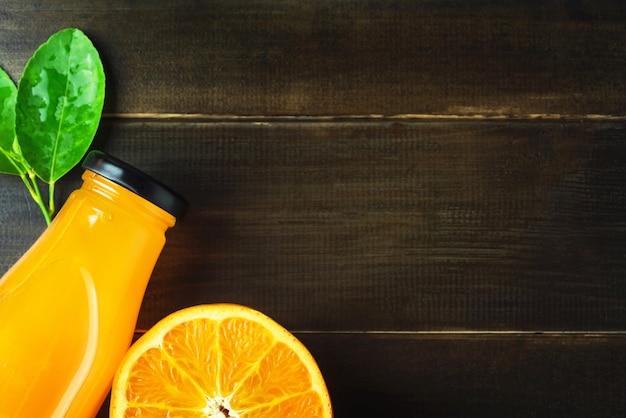 Vista superior de zumo de naranja fresco y frutas en rodajas en una mesa de madera con copia espacio
