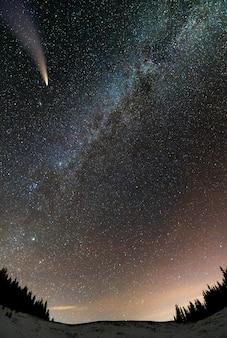 Vista surrealista de la noche en las montañas con cielo nublado azul oscuro estrellado y cometa c / 2020 f3 (neowise) con cola de luz.