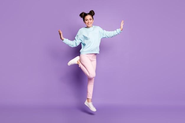 Vista del tamaño del cuerpo de cuerpo entero de agradable atractivo bastante delgado ajuste alegre alegre alegre niña saltando divirtiéndose bailando ocio aislado sobre fondo de color vibrante violeta púrpura lila brillante brillo vivo