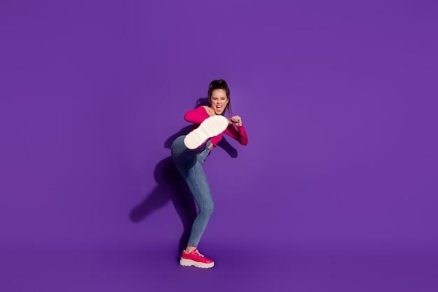 Vista del tamaño del cuerpo de longitud completa de una chica alegre fuerte luchando contra el enemigo invisible aislado sobre fondo de color violeta brillante