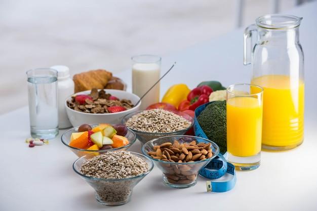 Vista del tazón de cereales, ensalada de frutas y comida en una mesa blanca