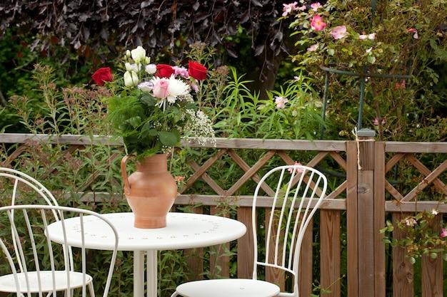 Vista a la terraza del jardín con muebles y flores.