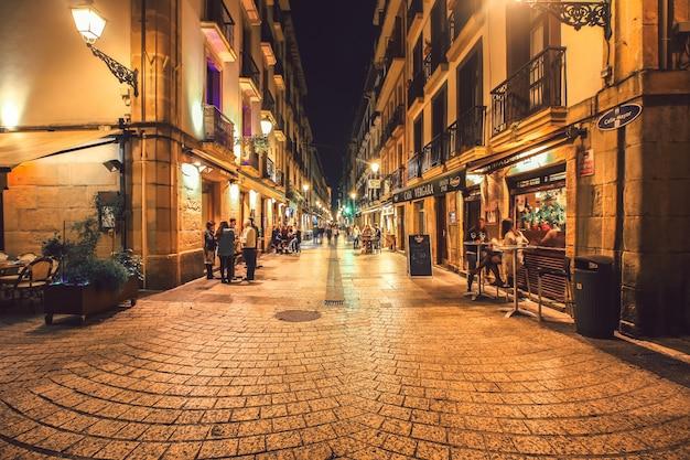 Vista típica de la calle pequeña de san sebastián con animados bares de tapas y restaurantes por la noche.