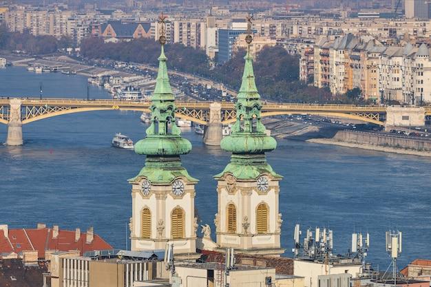 Vista de las torres de la iglesia parroquial de saint anne y el río danubio en budapest, hungría
