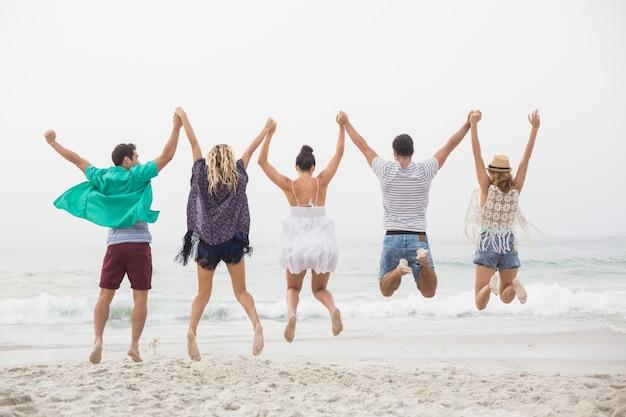 Vista trasera de amigos tomados de la mano y saltando en la playa