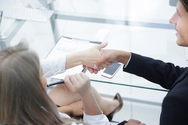 Vista trasera. apretón de manos de socios financieros después de la discusión del plan de negocios. el concepto de asociación