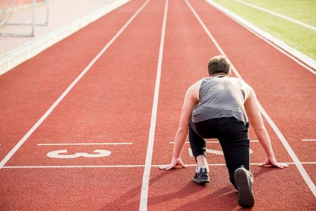 Vista trasera del atleta masculino listo para comenzar la carrera de relevos en la pista de atletismo