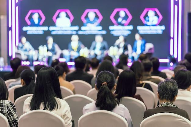 Vista trasera de la audiencia asiática que se une y escucha al grupo de oradores hablando en el escenario