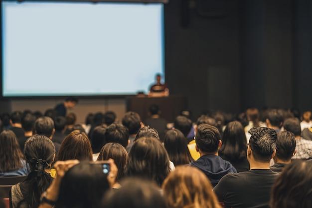 Vista trasera de la audiencia asiática que se une y escucha al orador hablando en el escenario del seminario