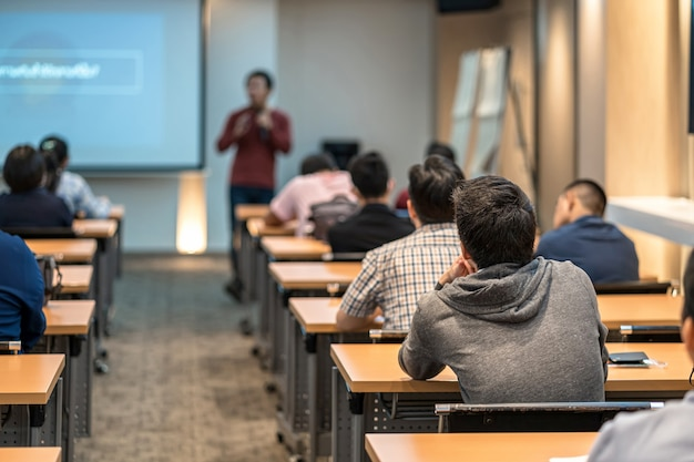Vista trasera de la audiencia escuchando al orador asiático en el escenario de la sala de reuniones