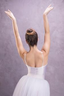 Vista trasera de la bailarina con las manos arriba.