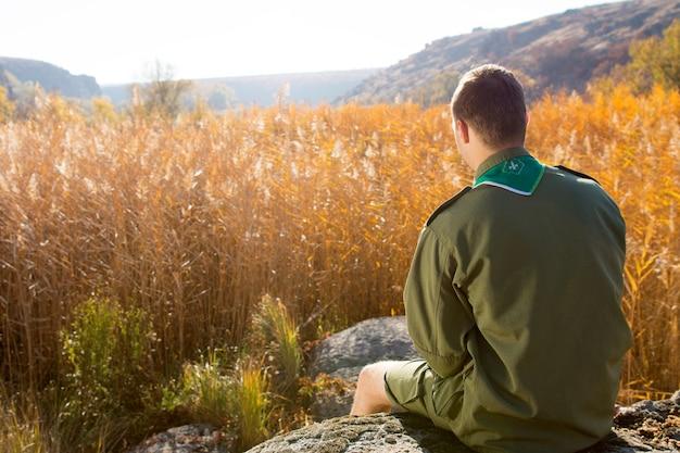 Vista trasera del boy scout blanco sentado en la enorme roca solo mirando el amplio campo marrón en una temporada de otoño.