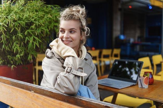 Vista trasera de una chica muy sonriente sentada en un café al aire libre y mirando a los transeúntes, mirando a la calle, tomando un descanso.