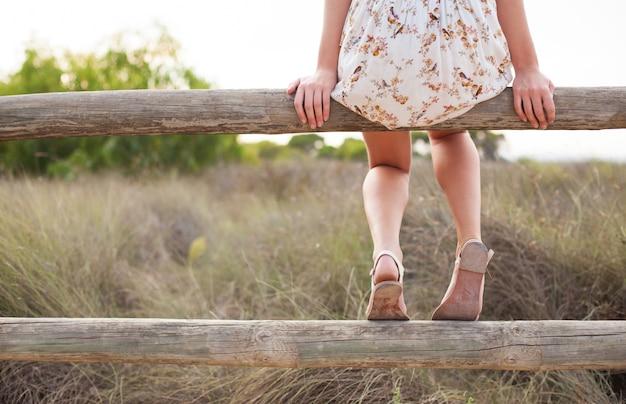 Vista trasera de chica sentada en una barandilla de madera