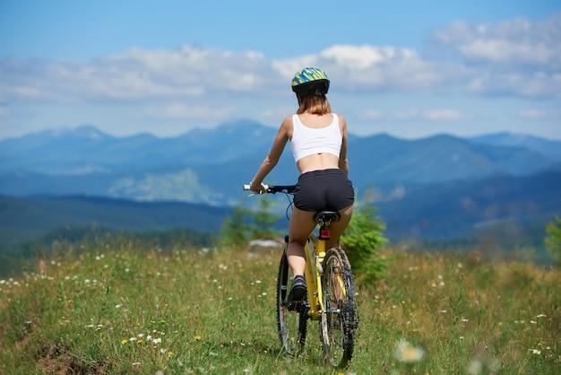 Vista trasera del ciclista deportivo femenino ciclismo en bicicleta de montaña amarilla sobre un césped