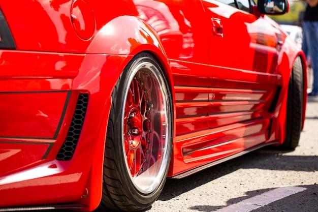 Vista trasera del coche sintonizado deportivo rojo de la rueda
