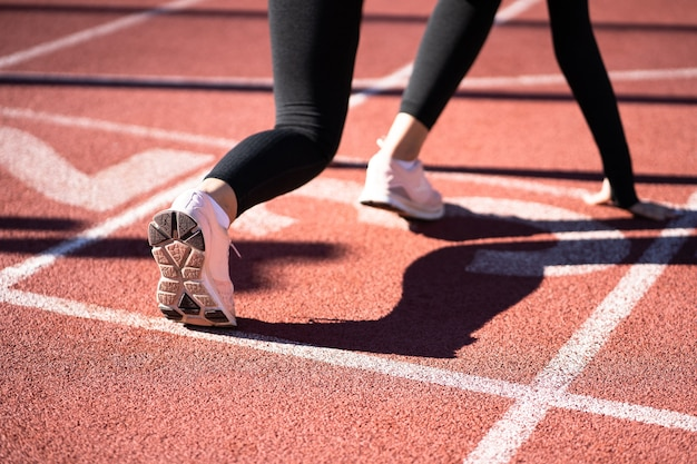 Vista trasera del corredor de la mujer en la pista de atletismo preparándose para comenzar a correr