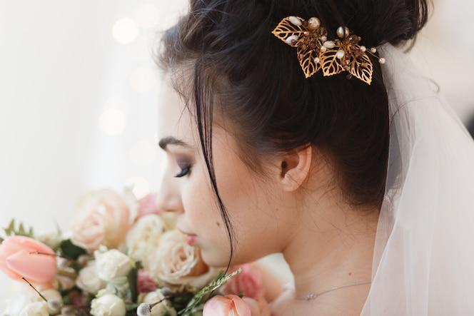 Vista trasera de la joven novia morena con pasador en el cabello. ramo de flores en el fondo
