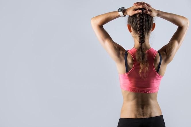 Vista trasera de la muchacha del ajuste con el cuerpo atlético