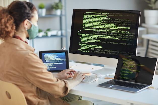 Vista trasera del desarrollador con máscara protectora sentado en la mesa frente a las computadoras e instalando el programa