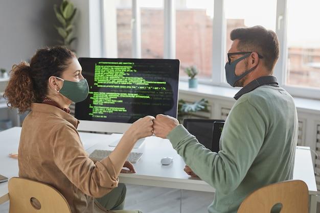 Vista trasera de dos desarrolladores con máscaras protectoras saludándose antes de su trabajo en equipos de oficina