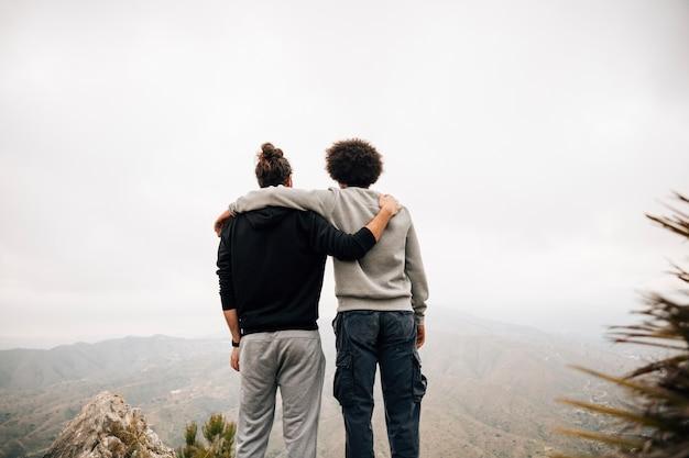 Vista trasera de dos excursionistas masculinos con vistas a la vista a la montaña