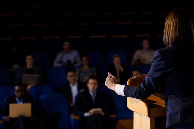 Vista trasera del ejecutivo de negocios femenino dando un discurso
