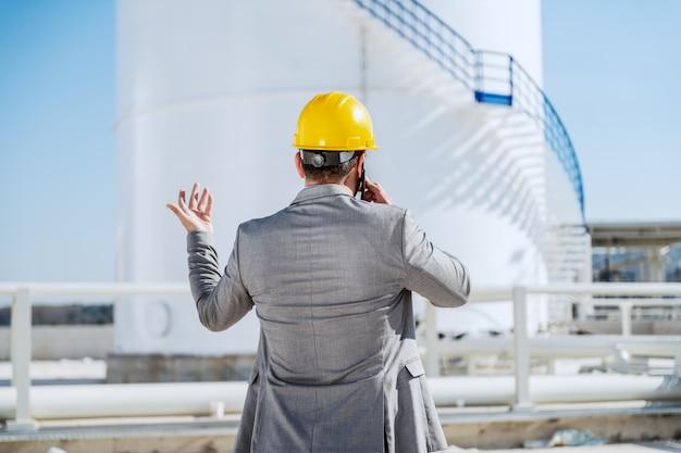 Vista trasera del empresario caucásico guapo en traje y con casco en la cabeza hablando por teléfono mientras está de pie al aire libre.