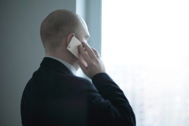 Vista trasera .empresario con smartphone mirando por la ventana de la oficina.foto con espacio de copia