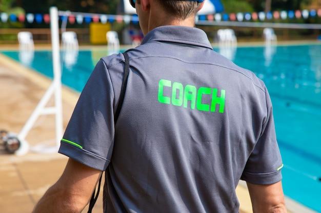 Vista trasera del entrenador deportivo de natación caminando por la piscina