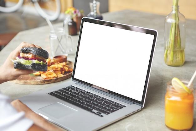 Vista trasera del estudiante sentado delante de una computadora portátil genérica abierta con una hamburguesa en la mano