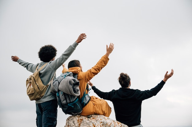 Vista trasera de excursionistas estirando sus manos mirando la vista