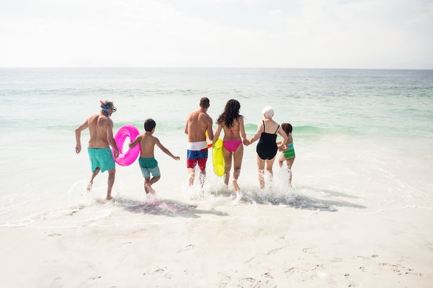 Vista trasera de la familia corriendo hacia el mar