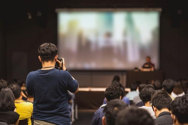 Vista trasera del fotógrafo tomando fotos de oradores asiáticos hablando en el escenario del seminario