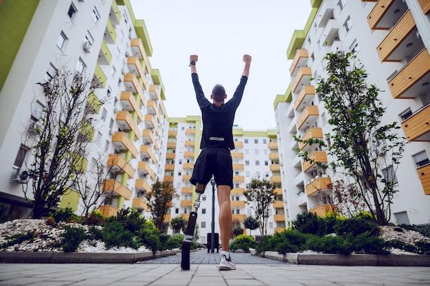 Vista trasera del guapo deportista con pierna artificial de pie con las manos en el aire al aire libre rodeado de edificios.