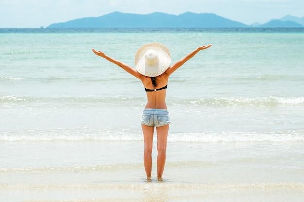 Vista trasera de una hermosa joven morena con las manos levantadas, mirando al mar. concepto de libertad