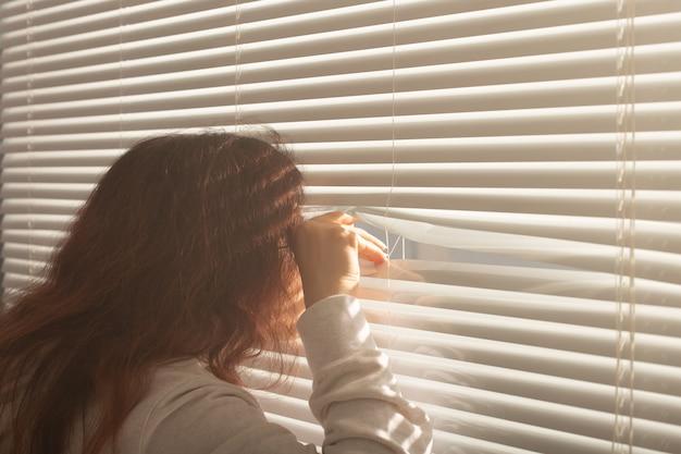 Vista trasera de la hermosa joven con el pelo largo se asoma a través del agujero en las persianas de la ventana y mira por la ventana. concepto de vigilancia y curiosidad
