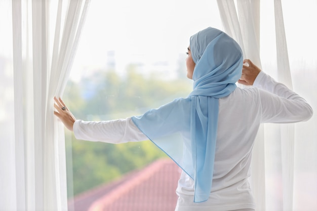 Vista trasera hermosa mujer musulmana asiática vistiendo ropa de dormir blanca, estirando los brazos después de levantarse por la mañana al amanecer. linda mujer joven con hijab azul de pie y relajante mientras mira lejos