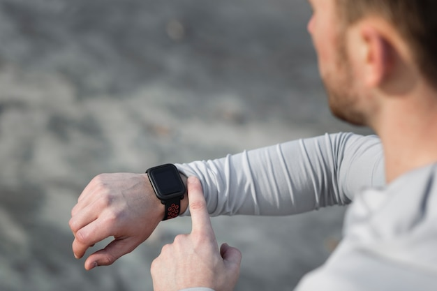 Vista trasera hombre ajustando su reloj deportivo