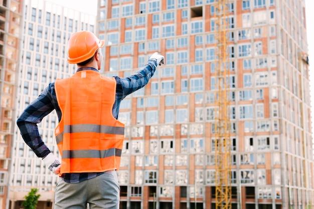 Vista trasera del hombre apuntando al edificio