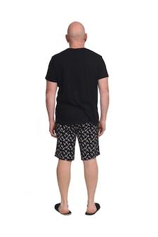 Vista trasera del hombre calvo en pijama corto sobre fondo blanco.