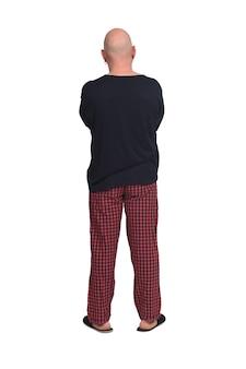 Vista trasera del hombre calvo en pijama sobre fondo blanco, con los brazos cruzados