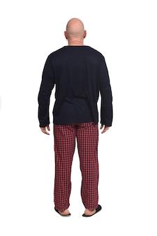 Vista trasera del hombre calvo en pijama sobre fondo blanco.