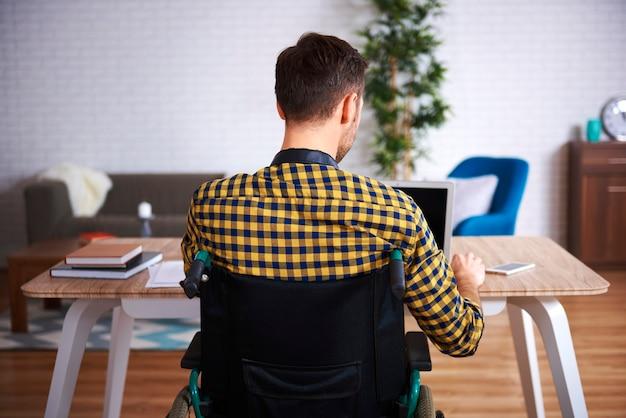 Vista trasera del hombre discapacitado usando laptop