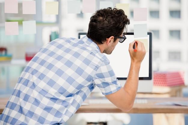 Vista trasera del hombre escribiendo en notas adhesivas