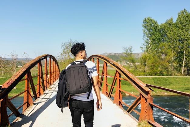Vista trasera del hombre joven que camina en el puente sobre el río hermoso