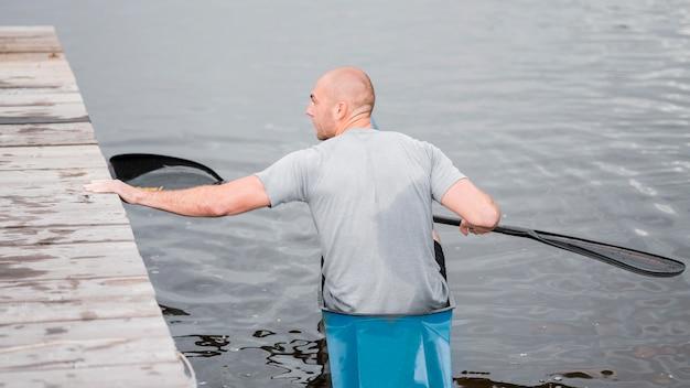 Vista trasera del hombre en kayak con remo