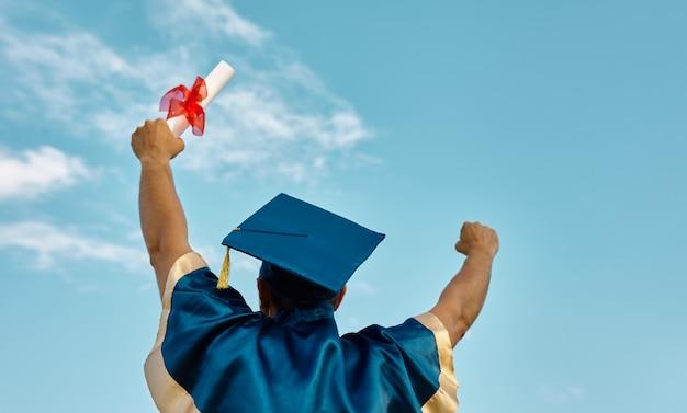 Vista trasera del hombre lanzando las manos hacia arriba un certificado y gorra en el aire, día de graduación en el fondo del cielo