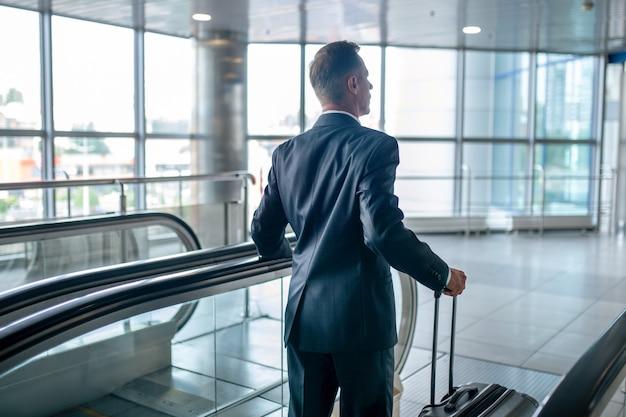 Vista trasera, de, hombre, con, maleta, en, escalera mecánica