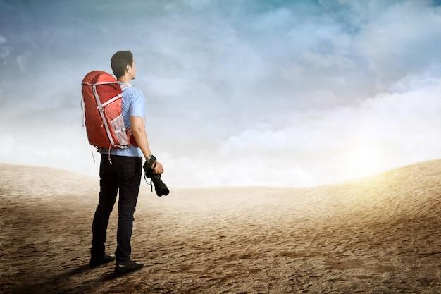 Vista trasera del hombre mochilero asiático con cámara